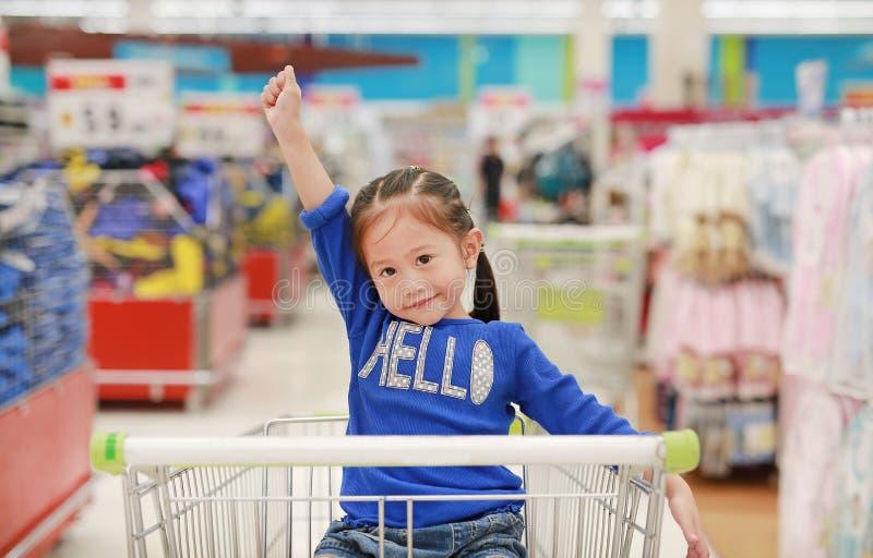 坐在台车的愉快的亚裔小孩女孩在家庭购物期间在市场上 免版税库存照片