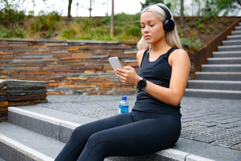 坐在台阶的美丽的体育妇女听到从智能手机的音乐 免版税库存图片
