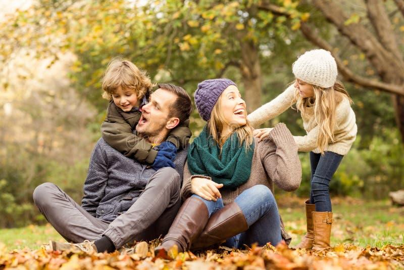 坐在叶子的微笑的年轻家庭 库存照片