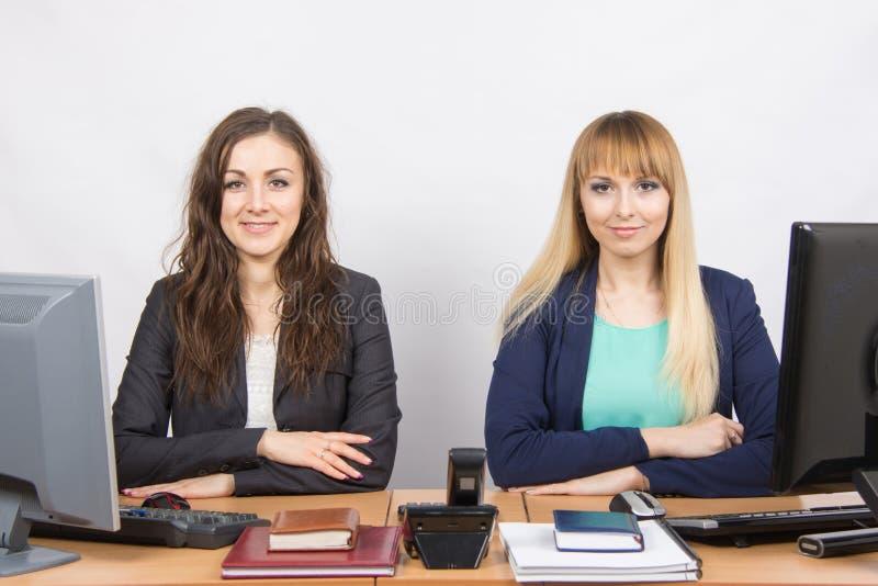 坐在同事办公室桌上的两个女孩被划分成两个工作 免版税库存图片
