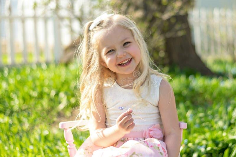 坐在后院的逗人喜爱的女孩 图库摄影