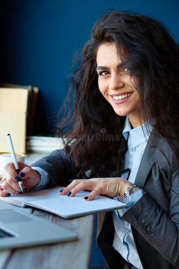 坐在咖啡店和写笔记的妇女 免版税图库摄影