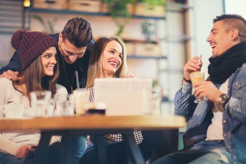 坐在咖啡店的小组青年人 免版税图库摄影