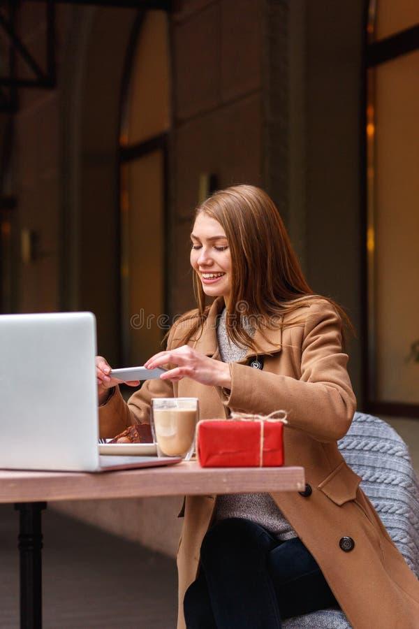 坐在咖啡店的少妇 她采取她的在电话的点心 在桌上是膝上型计算机 外面 库存照片