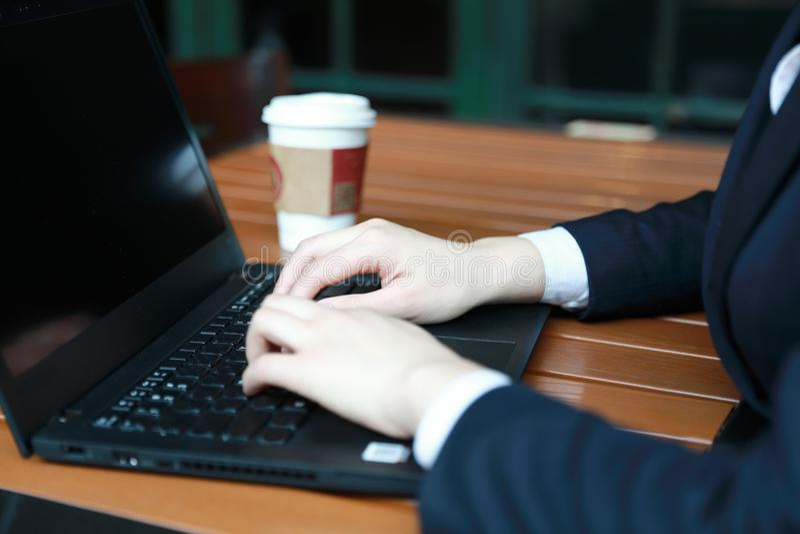 坐在咖啡店的年轻女商人在木桌,饮用的咖啡上 在桌上是膝上型计算机 库存照片