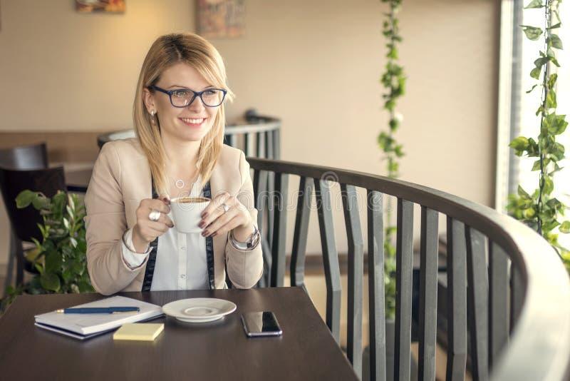 坐在咖啡店,饮用的咖啡和考虑某事的年轻微笑的女商人 免版税库存照片