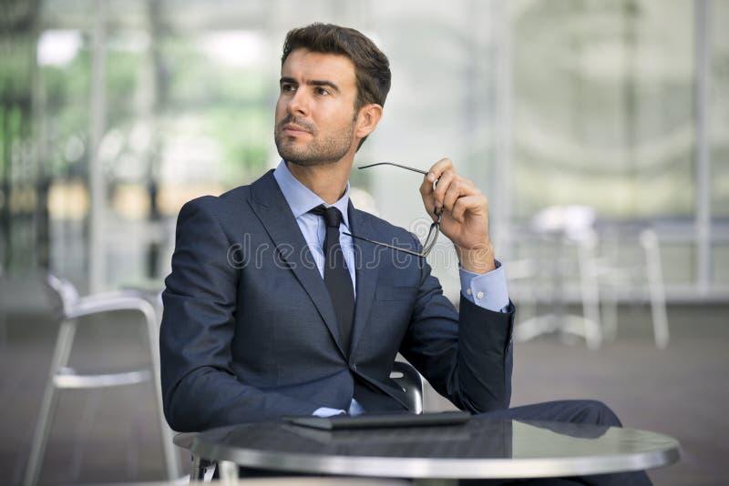 坐在咖啡店画象的商人 免版税库存图片