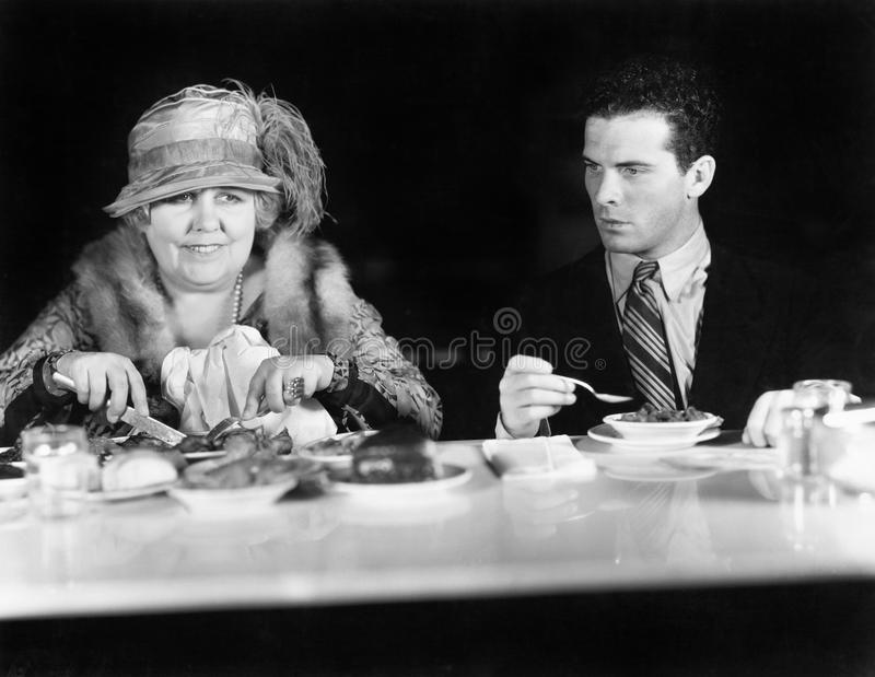 坐在咖啡柜台的妇女和年轻人(所有人被描述不更长生存,并且庄园不存在 供应商warran 库存图片