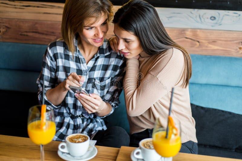 坐在咖啡馆、饮用的咖啡和ju的两个年轻女性朋友 免版税库存图片