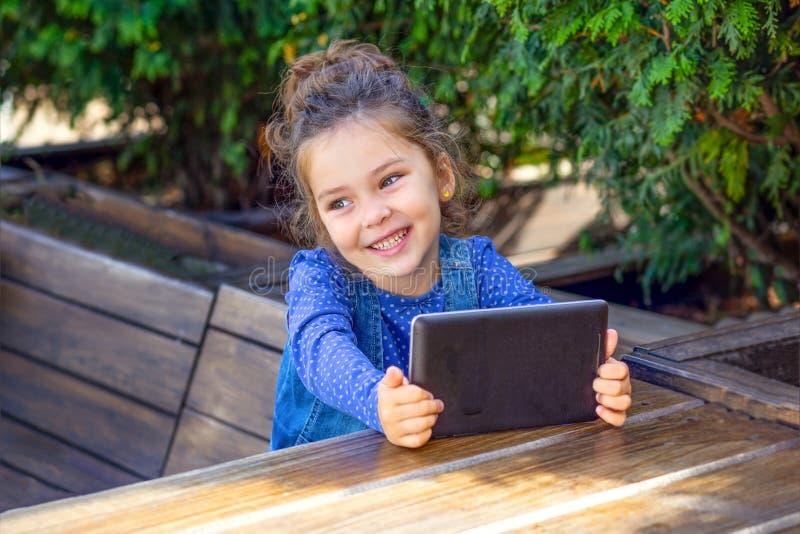坐在咖啡馆和使用在片剂的女孩 库存照片