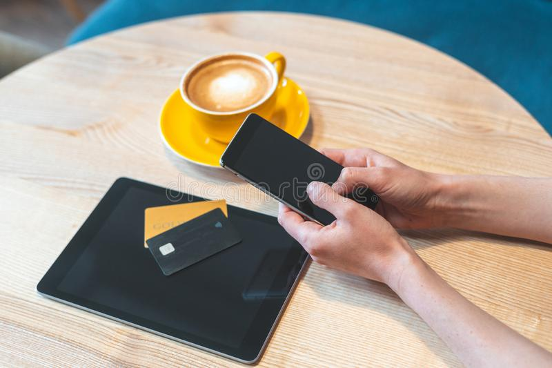 坐在咖啡馆和使用智能手机、片剂和信用卡的年轻女人 免版税库存图片