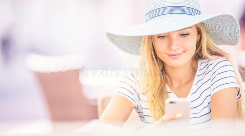 坐在咖啡馆和使用智能手机的年轻美女 免版税库存照片