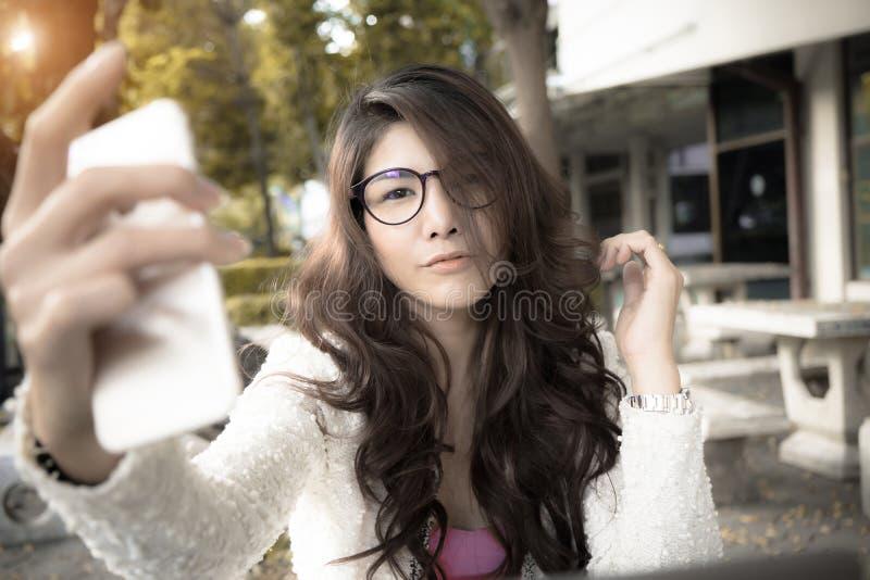坐在咖啡馆和使用机动性的可爱的年轻女商人 免版税图库摄影