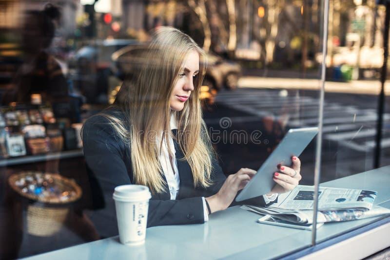 坐在咖啡馆和使用片剂个人计算机的女商人和饮用的咖啡 免版税库存图片