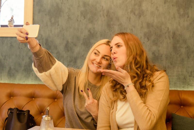 坐在咖啡馆和做selfie丝毫巧妙的电话的两个女孩 图库摄影