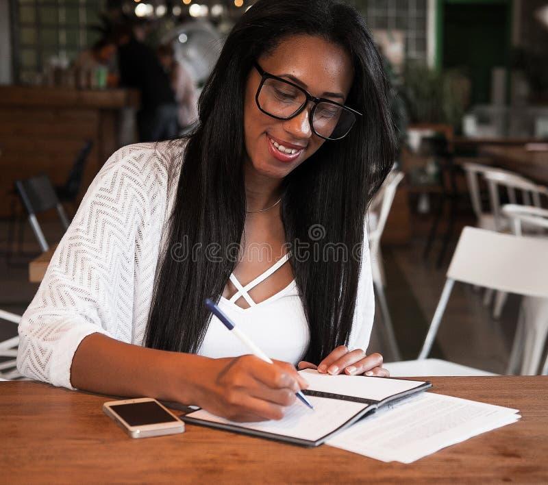 坐在咖啡馆和写笔记,生活方式概念的年轻黑人妇女 免版税库存照片