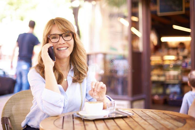 坐在咖啡馆和打电话的中间年迈的妇女射击  免版税图库摄影