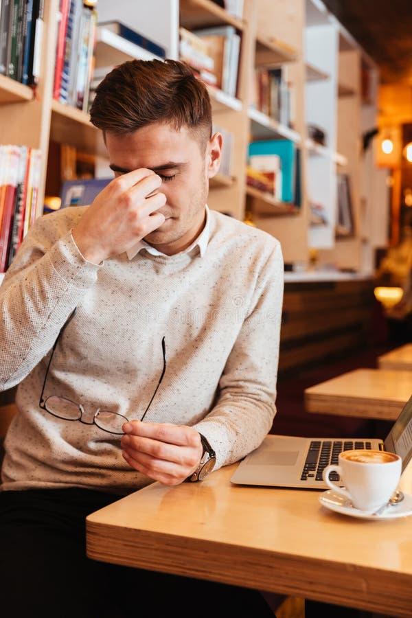 坐在咖啡馆和接触他的眼睛的疲乏的年轻人 免版税库存图片