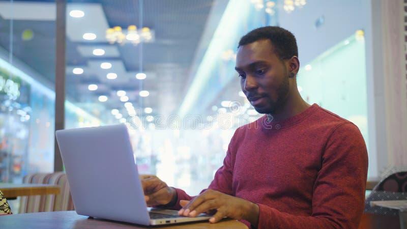 坐在咖啡馆和研究膝上型计算机的愉快的非洲商人画象  免版税库存照片