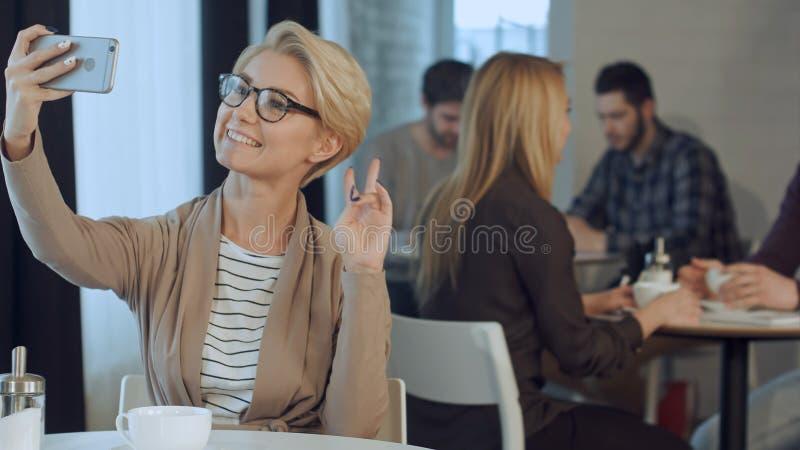 坐在咖啡馆和采取与她巧妙的电话的时髦的少妇佩带的玻璃画象selfie 免版税库存照片