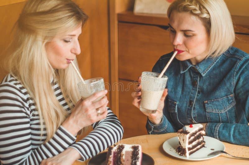 坐在咖啡馆和采取selfies的两名愉快的妇女在电话,喝鸡尾酒 库存照片