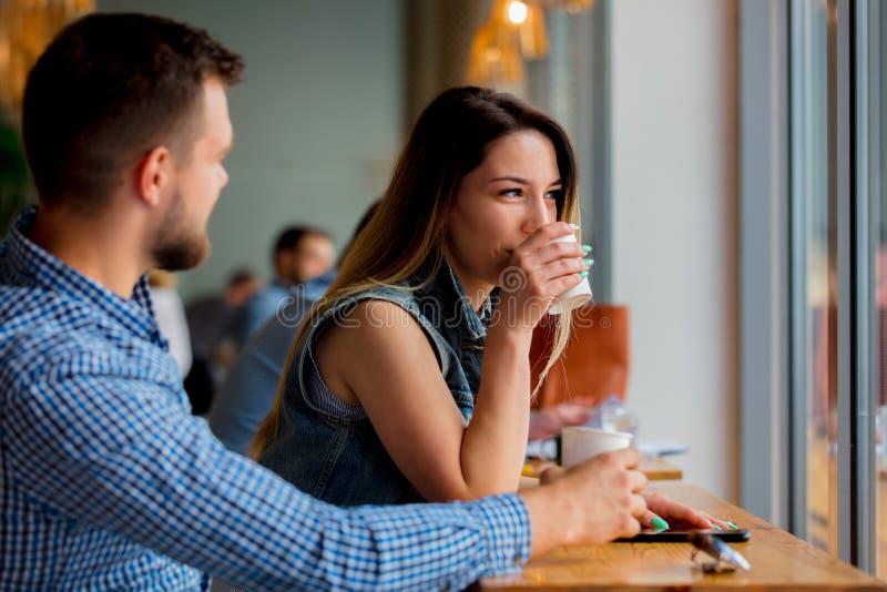 坐在咖啡馆和饮用的咖啡的一张桌上的夫妇 免版税库存图片