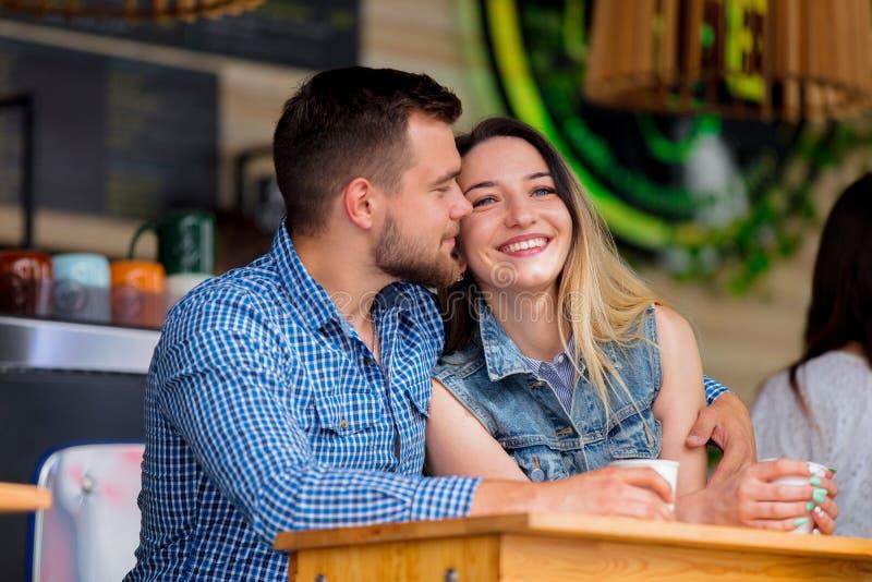 坐在咖啡馆和饮用的咖啡的一张桌上的夫妇 库存照片