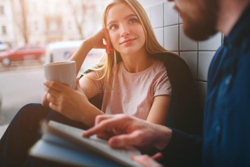 坐在咖啡馆在大窗口附近和看对她的男朋友的女孩 当他是时, Se听他非常仔细 库存照片