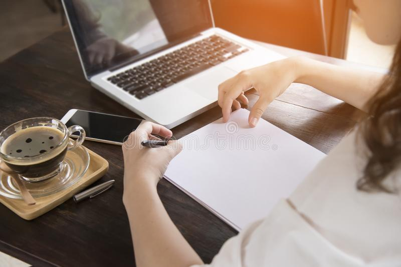 坐在咖啡馆在木桌,饮用的咖啡上和使用智能手机的年轻女人 在桌上是互联网购物的膝上型计算机 库存图片