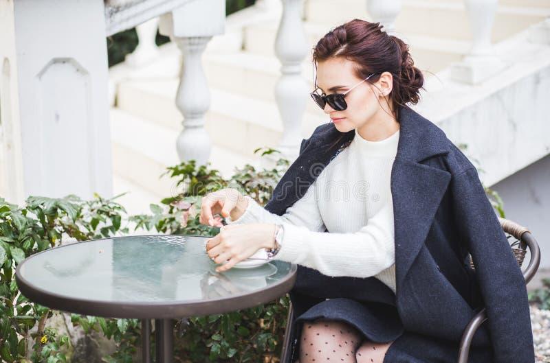 坐在咖啡馆室外饮用的咖啡的太阳镜的年轻时髦的美女 免版税库存照片