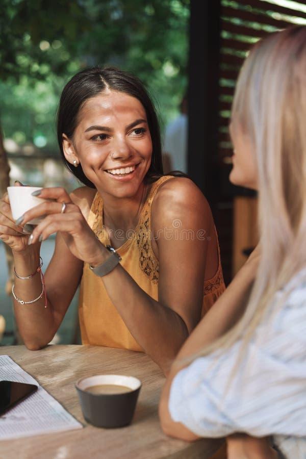 坐在咖啡馆桌上的两个快乐的年轻女朋友 图库摄影