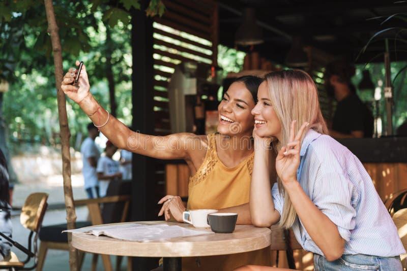 坐在咖啡馆桌上的两个快乐的年轻女朋友 免版税库存图片