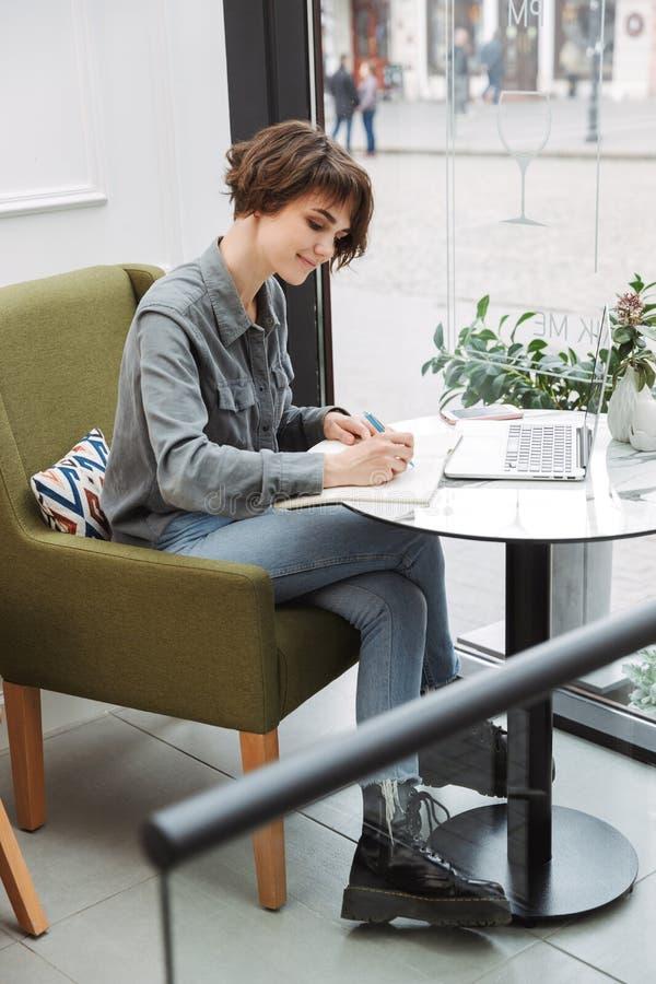 坐在咖啡馆桌上的可爱的年轻女人户内 免版税库存照片