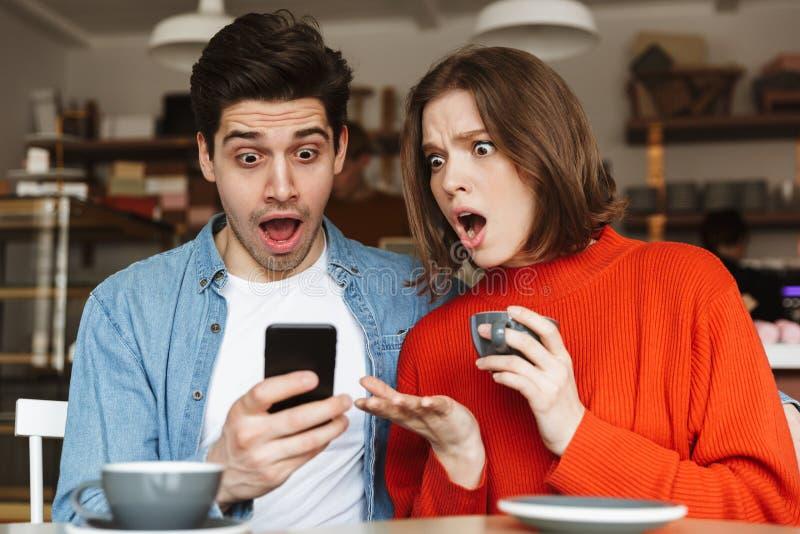 坐在咖啡馆桌上的震惊年轻夫妇 免版税库存图片