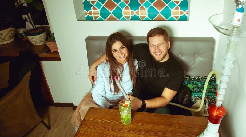 坐在咖啡馆的一张桌上的美好的夫妇 免版税图库摄影