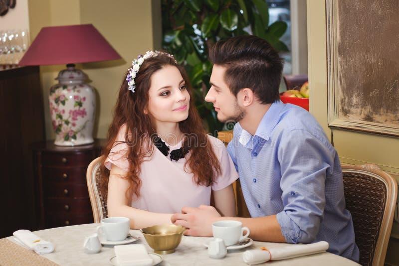 坐在咖啡馆的一张桌上的年轻美好的被迷恋的夫妇 免版税库存照片