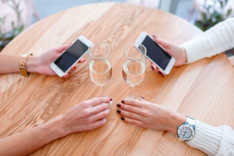 坐在咖啡馆的一张桌上,拿着巧妙的电话和喝香槟的女孩的手 库存照片