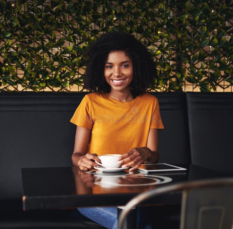 坐在咖啡馆的一微笑的年轻女人的画象 免版税库存照片