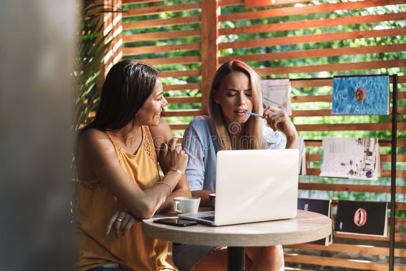 坐在咖啡馆的两个快乐的年轻女朋友户内 库存图片