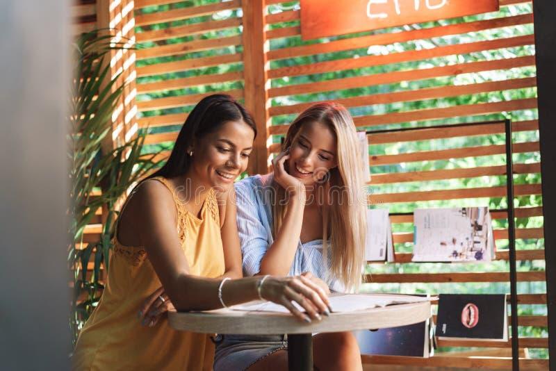 坐在咖啡馆的两个快乐的年轻女朋友户内 免版税库存照片