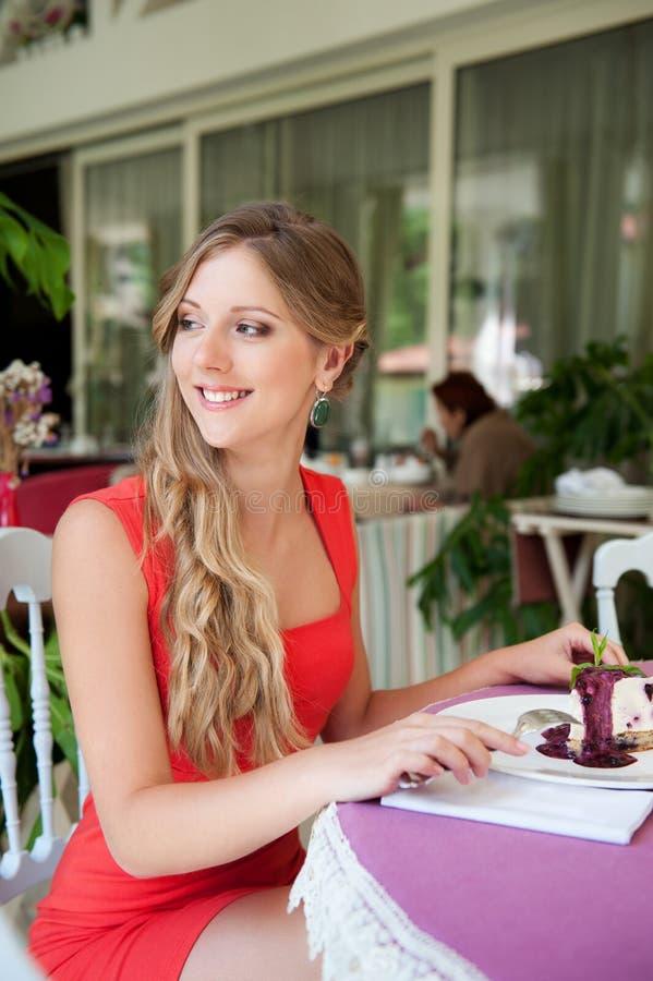 坐在咖啡馆的兴高采烈的妇女 免版税图库摄影
