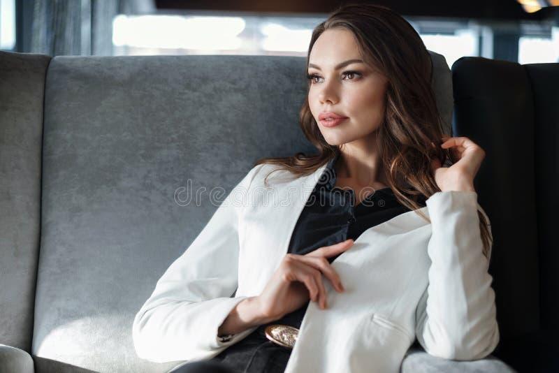坐在咖啡馆的妇女 在一杯咖啡的特写镜头在手中 免版税库存图片