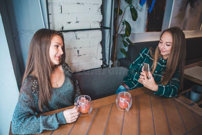坐在咖啡馆的妇女 拍在电话的女朋友照片,当喝温暖的果子茶时 库存图片