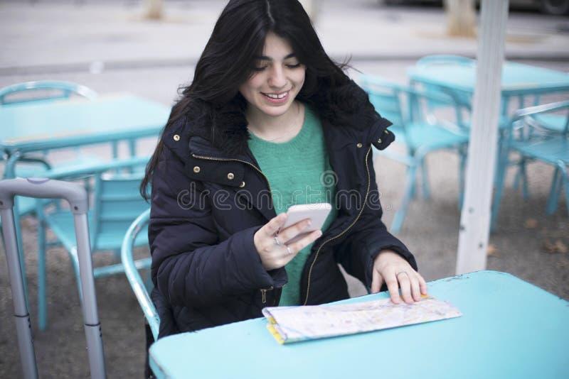 坐在咖啡馆的年轻女人游人户外,使用智能手机,拿着目的地地图 免版税库存图片