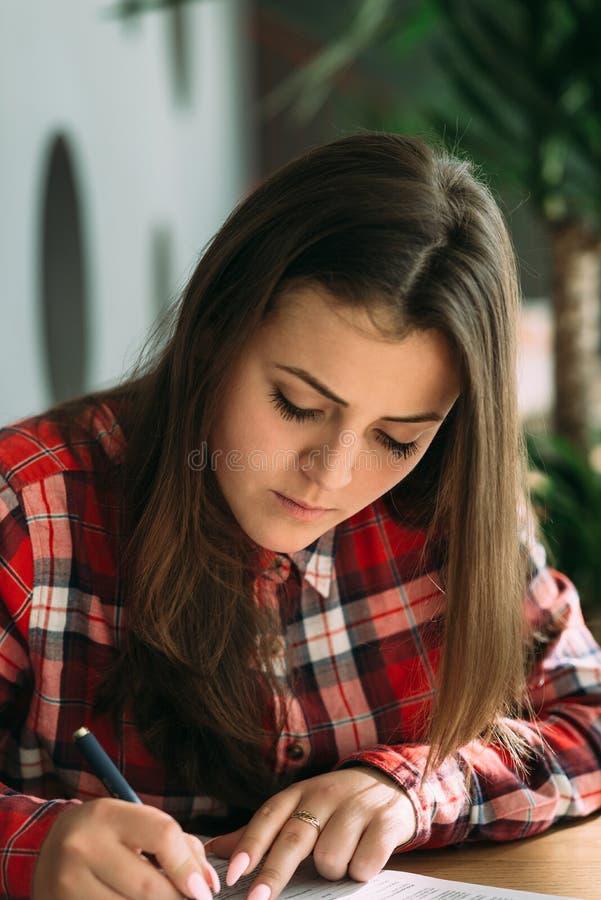 坐在咖啡馆的年轻美丽的女孩弯曲在桌和某事pishet 库存照片