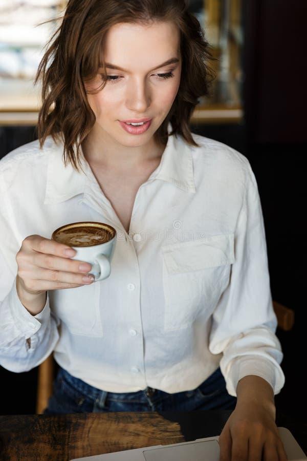 坐在咖啡馆的微笑的年轻女实业家户内 图库摄影