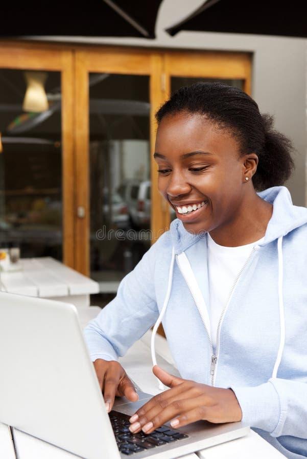 坐在咖啡馆的愉快的妇女谈话与网上朋友 库存照片