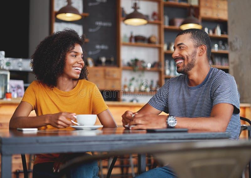 坐在咖啡馆的愉快的年轻夫妇 免版税库存照片
