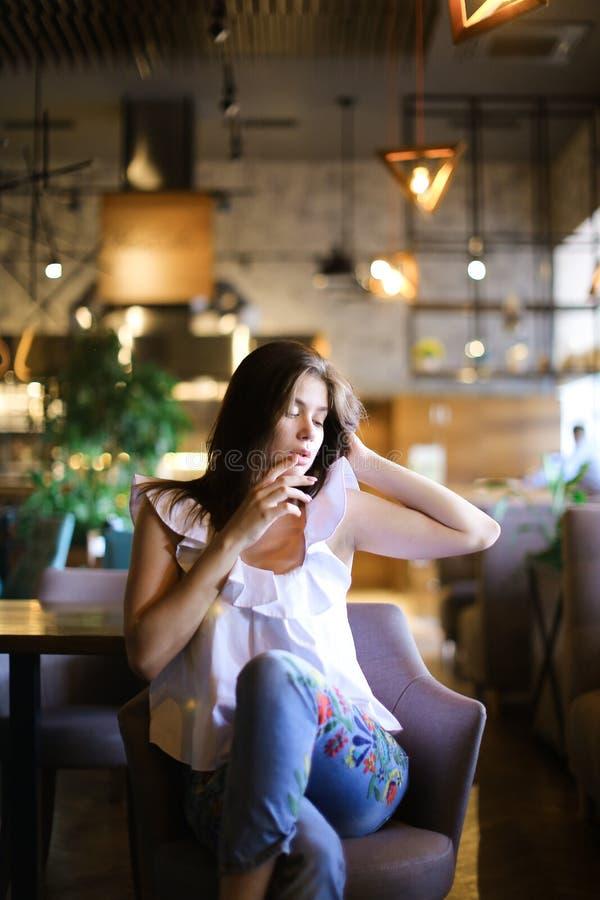坐在咖啡馆的时髦的白种人妇女用被举的手和佩带的白色女衬衫有种族牛仔裤的 免版税图库摄影