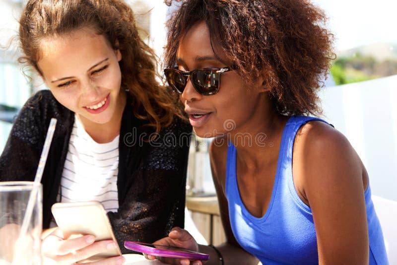 坐在咖啡馆的朋友看手机 免版税库存图片